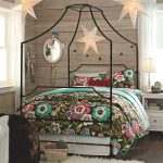 cute black iron canopy bed frame together with teenage comforter set adorned with star lanterns plus wooden wall and white fury rug plus nightstand and mirror
