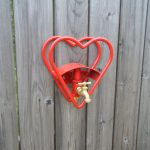 decorative-and-handmade-red-heart-garden-hose-holder-mounted-on-wooden-wall-with-materials-are-steel-and-brass-powder-coat-finish