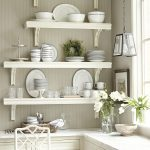 decorative-shelving-unit-for-kitchen-in-four-white-wooden-wall-mounted-shelves-on-grey-wall-near-white-window-and-pendant-lamp-over-white-wooden-cabinet-and-white-chair
