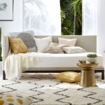 elegant and classy white gray daybed design with various cushions idea with grayand golden accent and chevron white area rug with wooden round small coffee table
