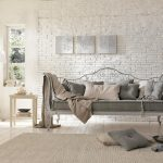 elegant and vinatge sofa design with gray upholster and metal frame and creamy area rug adn white brick wall accent and open plan