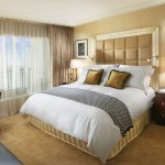 elegant classic creamy bedroom color idea with golden pillows and gray curtain idea with plaid textured headboard and wooden flooring and wall picture