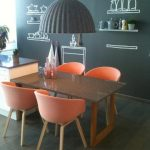 elegant coral colored chairs and wooden dining table with giant gray pendant and wooden floor and gray wall with racks