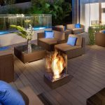 elegant outdoor patio design with wooden flooring and rattan sofa with blue cushions and glass box fireplace and pool with waterfall