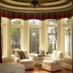elegant white bay window couch design with slipcover and round small coffee table and wooden floor and red patterned french curtain with curve style