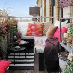 fancy apartment balcony furniture with sectional bench and colorful decorative pillows and round metal coffee table and solid wooden table and metal shelf and pretty plant