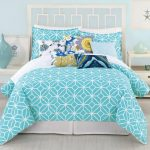 geometrical patterned turquoise bedding design with floral accent on white platform bed with white wooden side tables