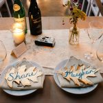 golden-leaf-placecard-from-fallen-leaves- on-each-plate-with-candles-and-flowers-centerpieces-and-bottles-on-the-table