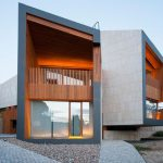 gorgeous architectural gray and orange two storey house design with open plan and wooden balcony and glass window