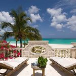 gorgeous beach stone balcony deisgn idea with two white pool chairs designs with concrete siding and beach view and coconut trees and small table with planter