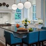 gorgeous big ball pendants above breakfast bar in a kitchen with blue stools and white cabinetry and glass window