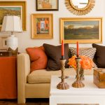 gorgeous interior design with wall pictures and mirror and creamy sofa with colorful cushions and candelabrums and orange storage