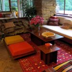 gorgeous orange and yellow moroccan floor cushion idea with pink patterned area rug and wooden coffee table and banquette and glass window and brick wall