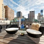 Gorgeous Outdoor Living Space With Black White Modern Couch With Brown Faux Throw And Wooden Floor Of Apartment With City View
