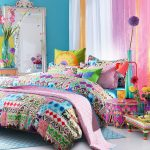gorgeous rainbow bedroom design idea with blue painted wall and potted orchid and pink sheer curtain and tribal patterned bedding and blue area rug and white flooring