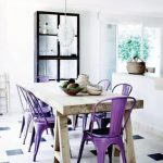 gorgeous rustic wooden dining table set with retro purple chairs and diamond patterned flooring and white pendnat and potted greenery