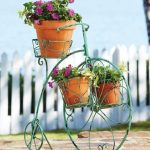 gorgeous unique bicycle wrought iron stand idea with orange potted plants  and green tone