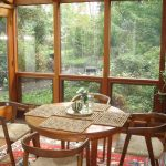 gorgeous vintage sunroom design idea with glass window and dining table set and wooden chairs and wooden table and indoor plant and patterned area rug