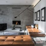 great minimalist interor design with caramel tone bench for seating with tuft texture and black chair and tv and wall pictures and wall lighting