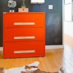 great orange walmart filing cabinet design with three drawers with sand clock and white square shaded table lamp beneath gray wall on wooden floor with cow print area rug