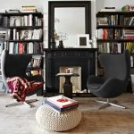 home library design idea with wall bookshelves and fireplace and black egg chairs and white rattan pouff and wooden floor