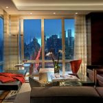 Livable Interior Design Of Apartment With City View With Creamy Patterned Curtain And Brown Sofa And Orange Throw And Glass Coffee Table