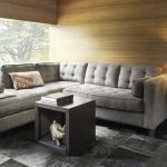 loft living room design with wooden siding and box coffee table with storage and gray patterner area rug and end table with table lamp and glass window