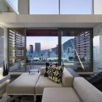 Luxurious And Modern Apartment With City View With Creamy Sofa Idea And Patterned Cushion And Wooden Floor And Double Height Interior