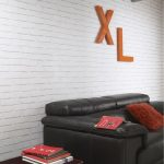 luxurious black leather sofa design with red cushion and big letter decoration on white brick wall acent