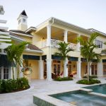 Luxurious Home Design Idea In White Color With Palm Trees And Pool And Concrete Patio Design And Stone Balcony Detail