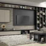 luxurious home library design with black wooden bookshelves and gray couch and media console and floating storage and white area rug