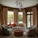 luxurious white bay window couch idea with orange cushions and orange table lamp and gray tufted sofa and floral round pouff coffee table