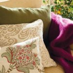 luxurous creamy sofa design with purple faux skin throw and rustic cushions with floral pattern in gray cream and green