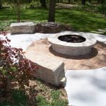 minimal outdoor patio design with round big firepit and concrete flooring and bench and grassy meadow and big trees and shrub