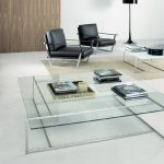 modern living room with rectangular small glass coffee tables together with stunning shelves and black leather chairs and beige rug plus black standing floor lamp and ottoman