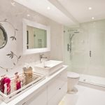 modern posh bathroom idea with glamor lighting and white glass tray set and framed round wall mirorr and wall pictures