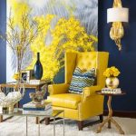monochrome yellow painting in the interior with navy blue painted wall and yellow wing chair and wooden table and white furry area rug