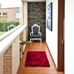 narrow corridor idea with large transparent glass window and red brick wall and wooden flooring and red runner rug and gray vintage chair with stone wall accent