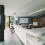 open plan kitchen studio design with white kitchen bar with wooden board and stools and glass window and sliding door
