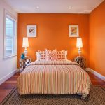 orange bedroom color ideas with stripe patterned beddig with stunning nighstands with table lamps and patterned area rug and white siding accent and wooden floor