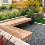 outdoor corner bench mounted on concrete wall plus pebble stones and green grasses for beautiful garden ideas