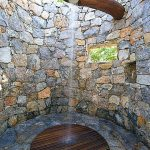 outdoor shower idea in rustic style with ceiling showerhead round wood shower flooring system built in shower shelf and natural stone wall system