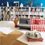 playful blue home library design with plus shaped jute rug and gray couch design with red french patterned throw and white bookshelves