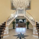 posh interior design with twin curving stairs with wire fence and giant chandelier and middle foyer idea