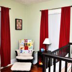 red blackout curtains nursery with large wooden baby crib and comfy white armchairs with stool and wooden nightstand with table lamp