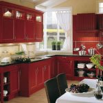 red country kitchen design with black top and white backsplash and white curtain and glass window and white dining table and black chairs and vased flower