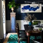 retro interior design with blue abstract painting on dark wall design with wooden dining table and green area rug