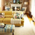 retro interior design with yellow sectional sofa and colorful coffee table and throw and white wing chairs and fireplace and double wallpaper decoration