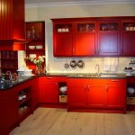 simple and small red country kitchen design with white siding and black top and wooden floor and backsplash cutlery hooks
