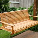 simple outdoor porch swing set made of wooden material with no furnishing and chain suspendion on wooden patio with grassy meadow
